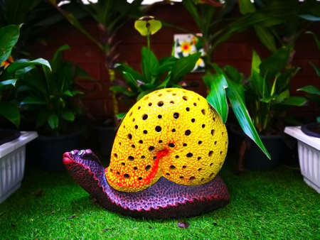 The colorful ceramic snail with yellow shell and purple body, which is on green artificial grass and decorated in a public small park. Selective focus and copy space.