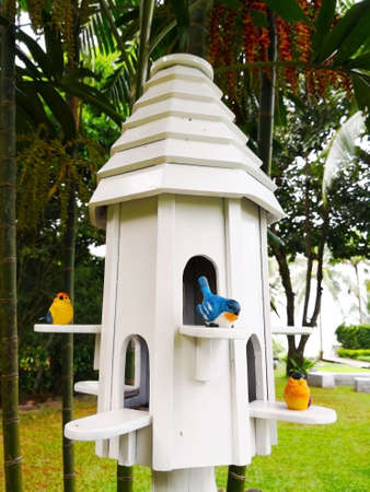 The white bird nest house with a blue bird and two yellow birds, there nestle on a small board at the window. It is decorated in the public park. Selective focus and copy space. Imagens