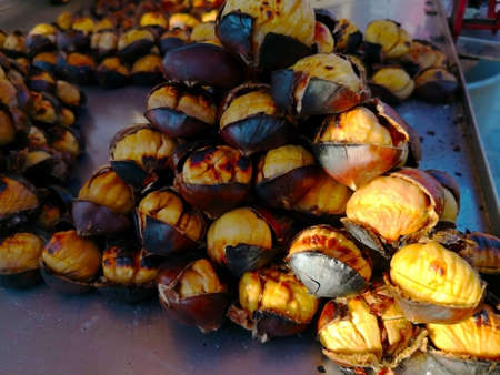 Food concept. Many large roasted chestnuts are stacked on stainless steel tray for sale at street food market. selective focus.