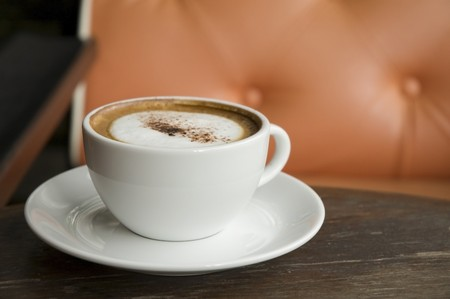 A cup of Cappuccino on wooden table with orange armchair background