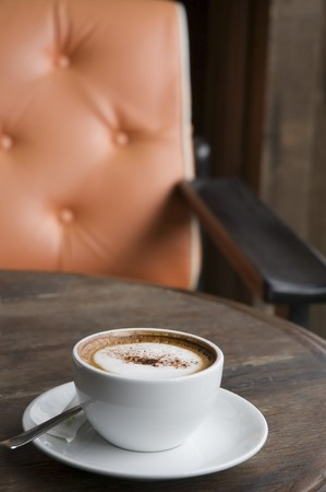 A cup of Cappuccino on wooden table with orange armchair background photo