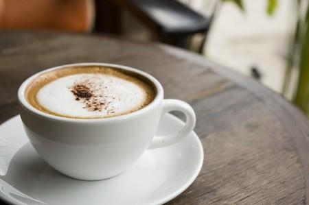 capuchino: Una taza de cappuccino caliente en tabla en caf� al aire libre