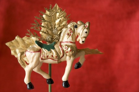 merry-go-round christmas ornament horse for decorate on red background.