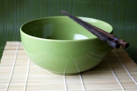 Green bowl and chopsticks on Bamboo pad. Stock Photo - 8387592