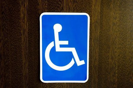 Handicap restroom signage on Oak wood background.