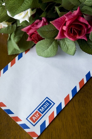 airmail: Blank airmail envelope and bouquet of roses Stock Photo