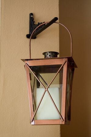 an old candle lantern hanging on a wall photo