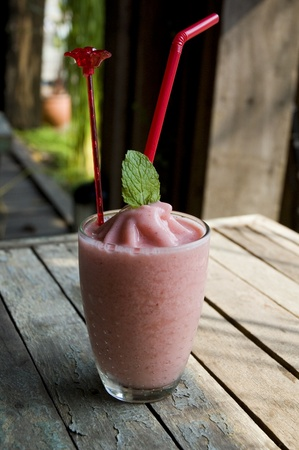 delicious refreshing strawberry yogurt put on outdoor wooden table.