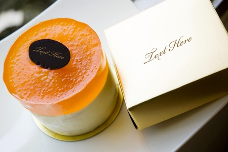 orange cake with golden box Stock Photo