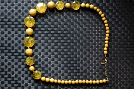 yellow crystal necklace on black texture background