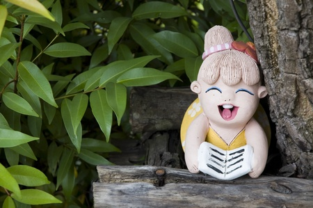 painted clay doll girl reading in garden photo