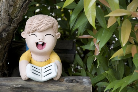 painted clay doll boy reading in the garden