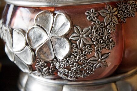 hand carved: silver floral handicraft detail on pink glass bowl