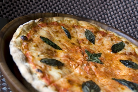 close up tasty pizza on wooden tray photo