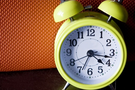 green color alarm clock with orange color background Stock Photo