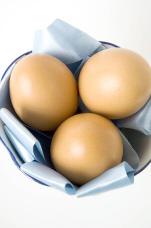 three of eggs put in blue paper on white background photo