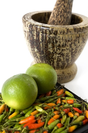 lime on hot chili with wooden mortar on white background Stock Photo
