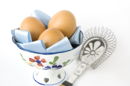 eggs in bowl with kitchenware on white background photo