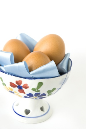 group of eggs in flower bowl on white background photo