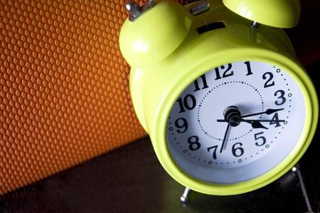 despertador: mirar hacia abajo en el reloj de alarma de color verde con fondo de color Foto de archivo