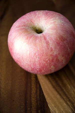 close up pink apple on wooden tray Stock Photo