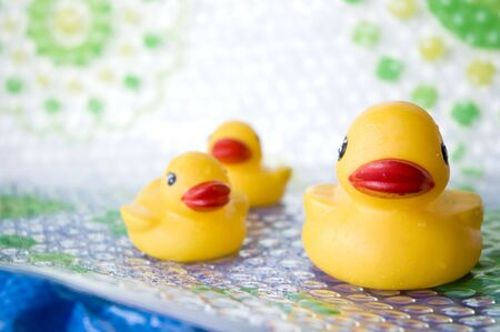 close up yellow duck family made from rubber for baby bath photo