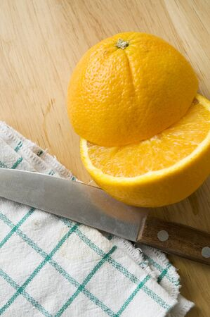 knife and half pieces of orange cut photo