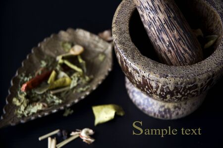 close up mortar and spices with sample text on black background photo