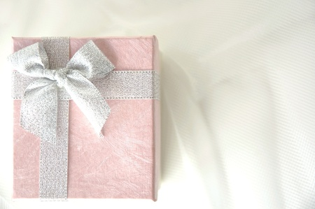 top view of pink gift box with silver ribbon on white photo