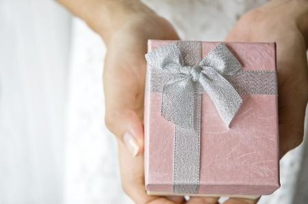 mains d'une femme tenant boîte cadeau rose