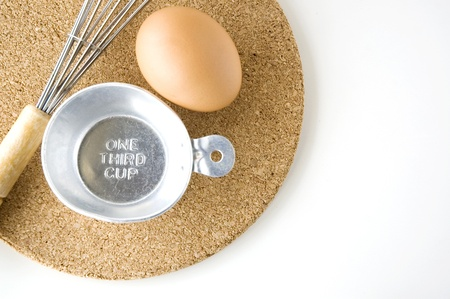 measuring one third cup with egg and whisk on board