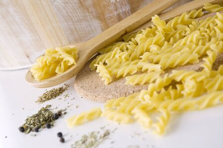 raw pasta on spoon with spices for cooking photo