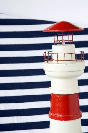 white and red lighthouse model with blue strips background
