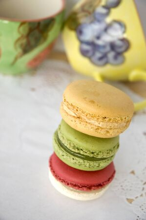 stack of colorful macarons with colorful cups background photo