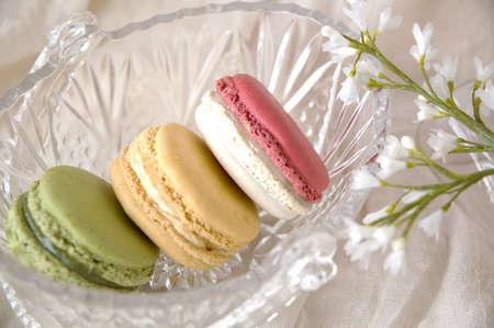 colorful macarons put in glass basket with little flowers photo