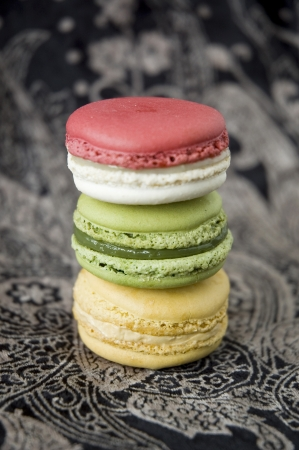three color macarons on black background photo