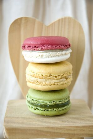 stack of macarons on wooden heart shape background photo