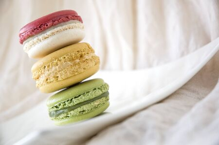 stack of sweet macarons on white plate photo