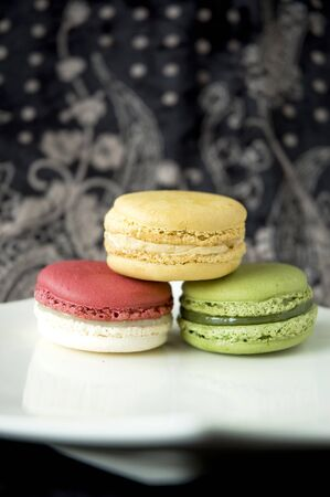three color macarons on white plate in black background photo