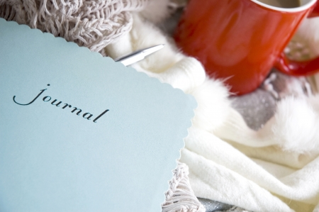 blue journal book put on desk with scarf and cup of coffee