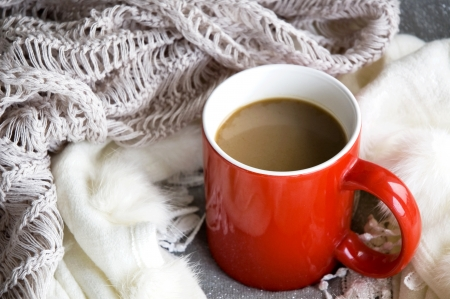 a cup of hot coffee with scarf around on winter Stock Photo