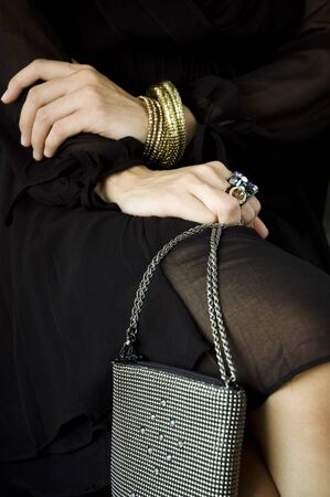 close up hands of woman sitting and holding her handbag photo