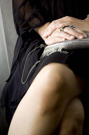 woman in black dress sitting crossed leg photo