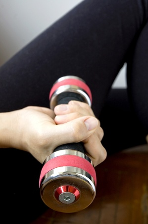 sporty woman is working out with dumbbell photo