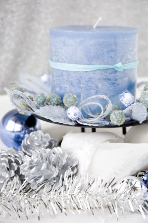 close up blue candle decorated with christmas ornaments