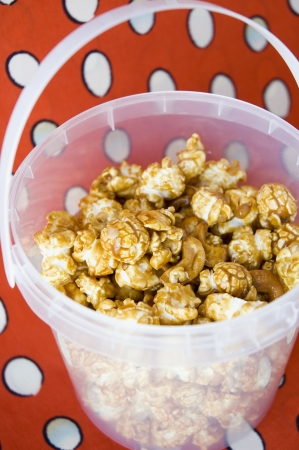 close up caramel popcorn in bucket with red background photo