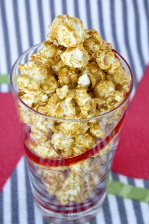 caramel popcorn in glass with colorful background photo