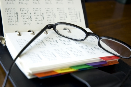 eyeglasses put on calendar page of personal organizer photo