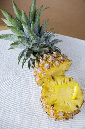 straw put in fresh pineapple with green leave photo