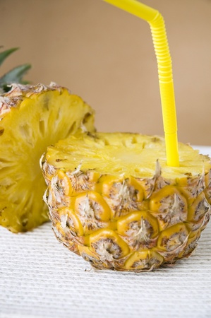 straw put in fresh pineapple for juice concept photo